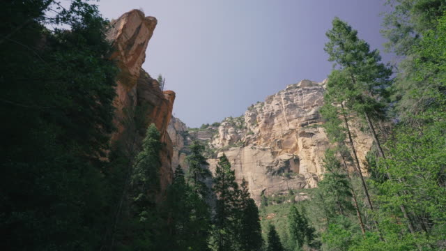 walking towards tall cliff - canyon stock-videos und b-roll-filmmaterial