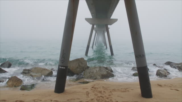 Walking under a rusty bridge that goes from the shore to the sea and the fog. The shot shows first the shoes on the sand and after discovers this wide powerful image.