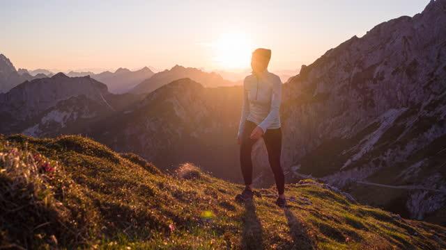 vídeos de stock e filmes b-roll de walking uphill in the mountains, illuminated by sunset light - em cima de
