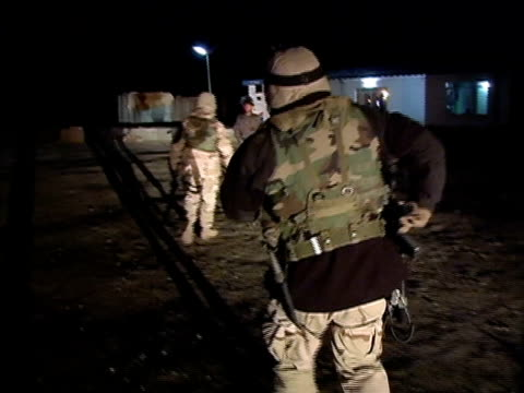 Walking POV US soldiers meeting Afghan police at night and shaking hands/ Afghanistan