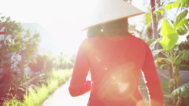 walking vietnamese female wearing red ao dai vietnam - 赤のドレス点の映像素材/bロール