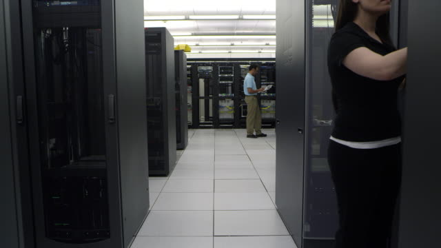 vídeos de stock, filmes e b-roll de walking view of three people working in network server room - câmera em movimento