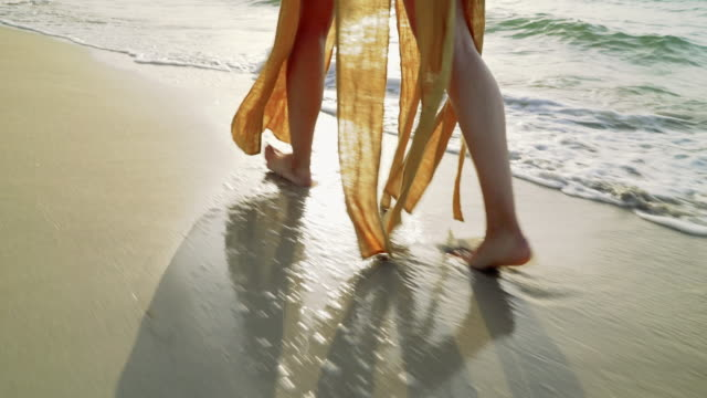 tracking shot: walking young woman's feet on the beach - coastal feature stock videos & royalty-free footage
