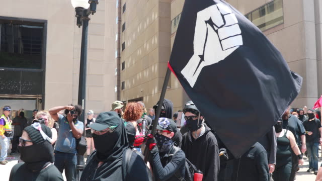 antifa walks in formation while protesting against the kkk protesters use cell phones to film the kkk arriving for a klan rally hundreds of counter... - ku klux klan stock videos and b-roll footage