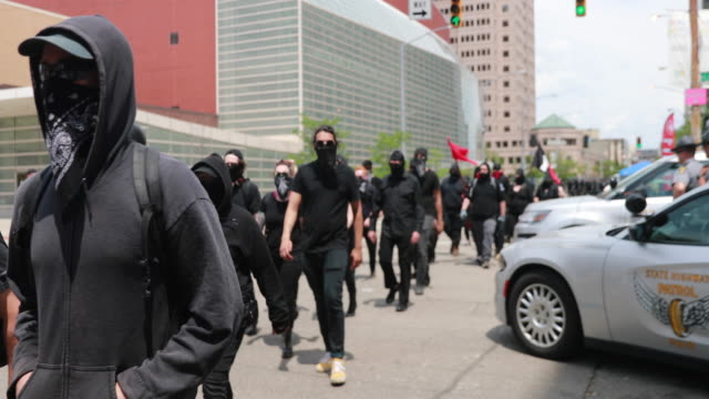 stockvideo's en b-roll-footage met antifa walks past police cars while looking for a way to confront members of the kkk who were holding a rally nearby and were about to leave the... - racisme
