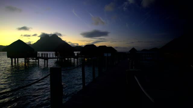 walkway at sunrise overwater luxury bungalows bora bora - polynesian ethnicity stock videos & royalty-free footage