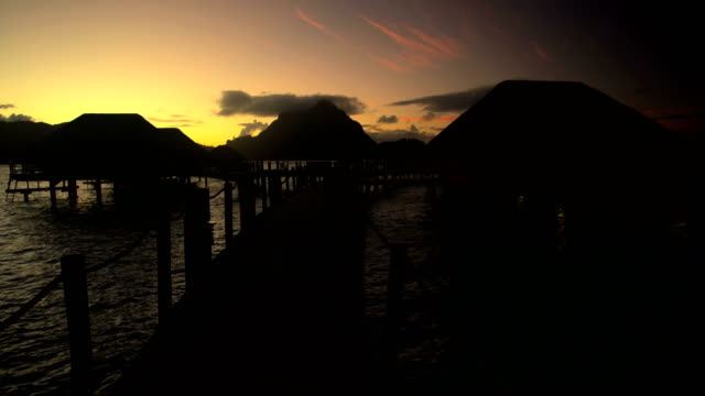 walkway at sunrise to overwater bungalows bora bora - polynesian ethnicity stock videos & royalty-free footage