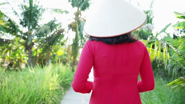 walkway through banana plantation with vietnamese female vietnam - 赤のドレス点の映像素材/bロール