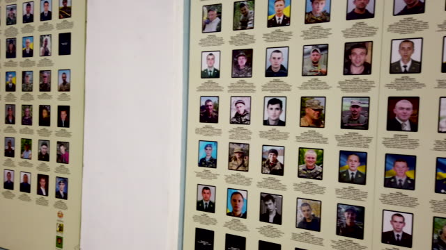 wall at st. michael's monastery stands covered with photos of the over 3,000 ukrainian soldiers killed so far in the war against russian separatists... - war stock-videos und b-roll-filmmaterial
