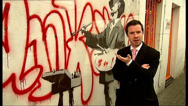 vídeos de stock e filmes b-roll de wall bearing banksy original for sale england london portobello road ext painting by grafitti artist banksy on wall protected by glass luti fagbenle... - portobello