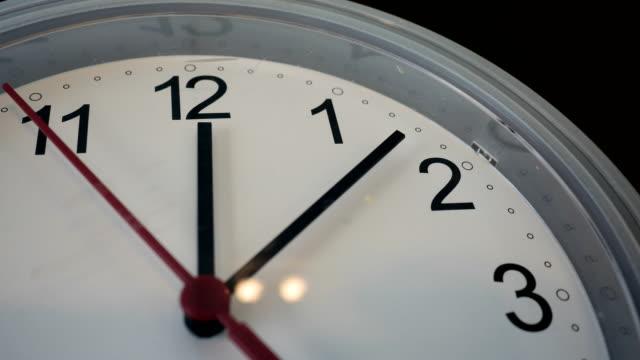 12 oclock 壁時計と赤いカチカチの矢印。4 k 解像度でプロのショット - 腕時計点の映像素材/bロール