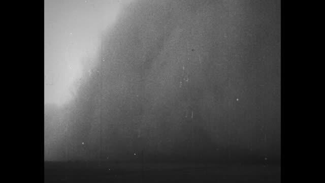 vidéos et rushes de vs wall of dust billows blocking out the sky during dust bowl dust storm / cow stands on desolate farmland as dust blows / note exact year not known... - tempête de poussière