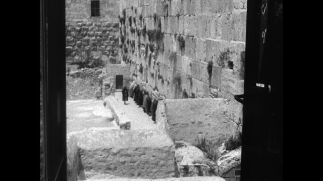 vídeos de stock e filmes b-roll de jerusalem wall of prayer west wall of the temple mount 'the wailing wall' w/ jewish people lined up praying face to wall face of praying male hands... - jerusalém