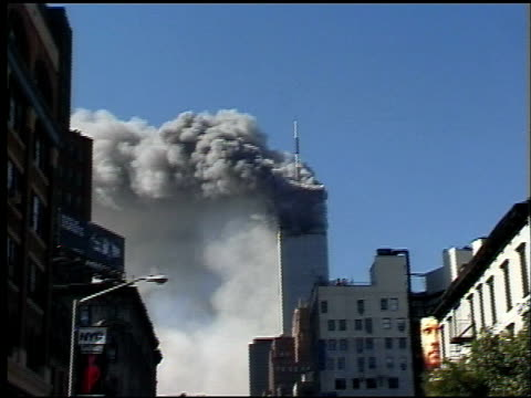 wall of smoke at wtc site of collapse / tower 1 obscured by smoke / people run and walk north on street / tower 1 burns following collapse of tower 2... - aereo militare video stock e b–roll