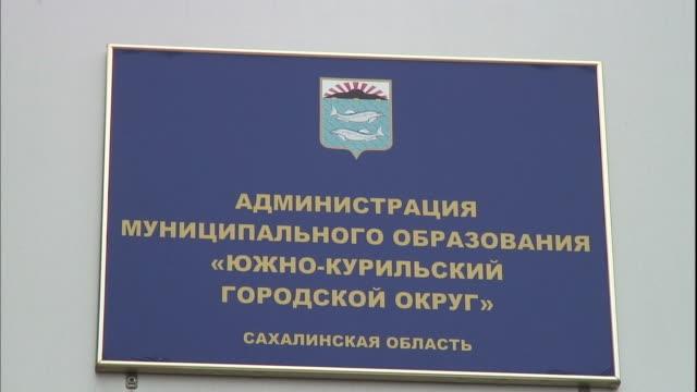 vídeos y material grabado en eventos de stock de wall plaques on a government office building at kunashiri island use cyrillic characters and display a south kuril flag. - señal de información