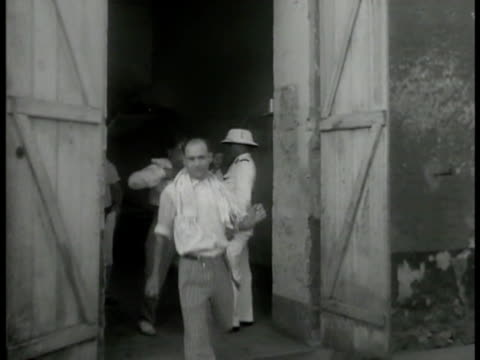vidéos et rushes de wall sign: 'la proprete c'est la sante' . morning wash: men walking out of building w/ towels. prisoners in stripped pants washing outside w/ water... - dom tom