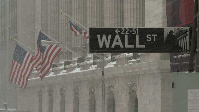 wall street and the new york stock exchange during a snowstorm - street name sign stock videos & royalty-free footage