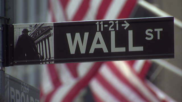 cu wall street sign with new york stock exchange with flags in background / new york city, new york, usa  - trading stock videos & royalty-free footage
