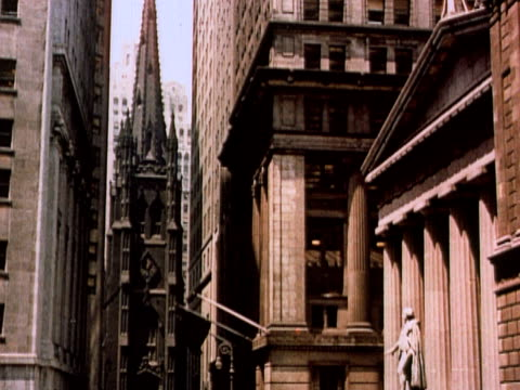 1960 TD WS Wall Street with view of Trinity Church and Federal Hall / crowded sidewalks and traffic / New York City