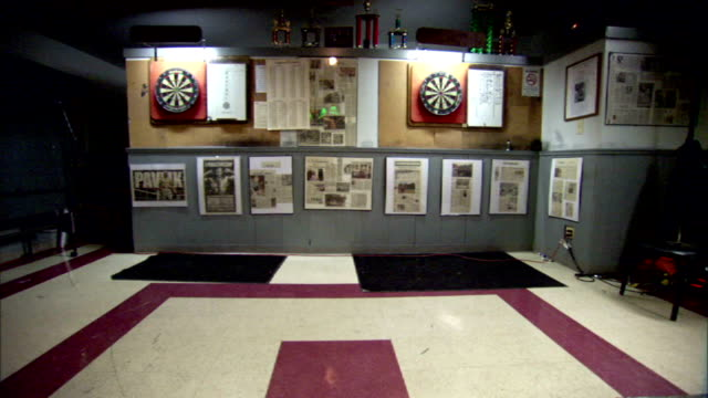 WS Wall w/ double darts boards newspaper clippings trophies on shelf above boards Tavern games social competition interaction skill