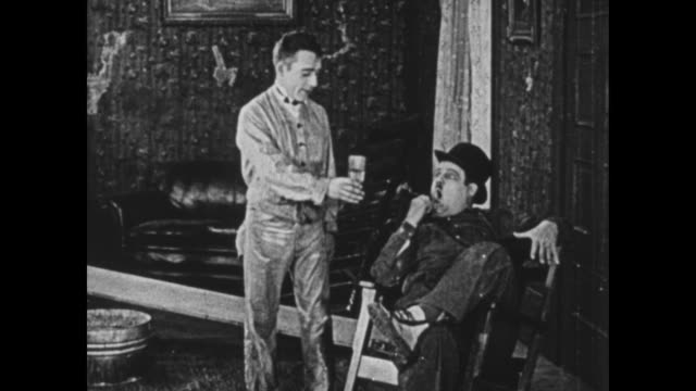 vidéos et rushes de 1925 wallpaper assistant gives his boss (oliver hardy) some water, which he drinks before throwing the glass on the ground - 1925
