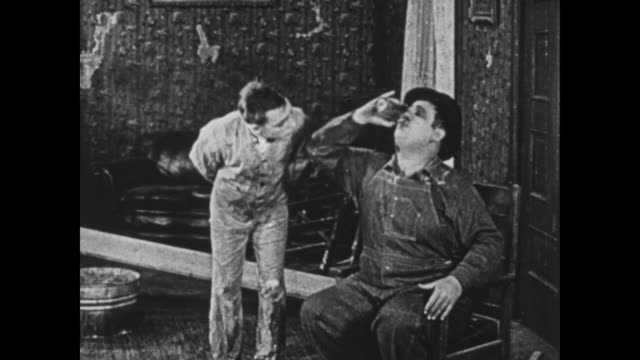 1925 Wallpaper helper gives his irritated boss (Oliver Hardy) a glass of water, which he gulps greedily