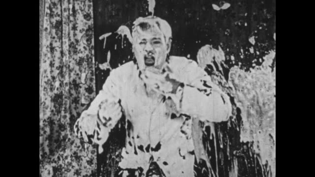 1925 wallpaper manager (oliver hardy) tries to remove paste bucket from his assistant's (bobby ray) behind and ends up spraying paste all over other man - glue stock videos and b-roll footage