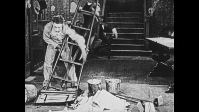 vidéos et rushes de 1925 wallpaper worker calmly pulls enormous amount of wallpapering supplies out of bag, seemingly with magical skills as his boss (oliver hardy) relaxes nearby - infini