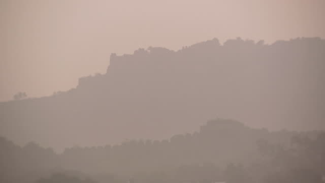 WS PAN Walls of Golconda Fort silhouetted against morning sky through fog / Hyderabad, Andhra Pradesh, India
