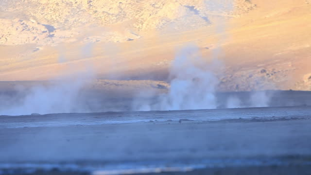 WS Walls of steam coming out from ground in bluish ground with light brown ground / Geiser del Tatio, Atacama desert, Chile