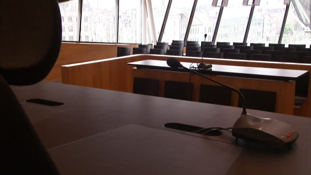 walls of windows in a courtroom shed light on spare, modern desks and chairs. - gerichtssaal stock-videos und b-roll-filmmaterial