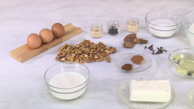 vídeos de stock e filmes b-roll de walnut and cinnamon cookie ingredients. pan on eggs, walnuts, milk, yeast, vegetable shortening, cinnamon, cloves, mahleb, sugar, oil, butter, flour. - ingrediente