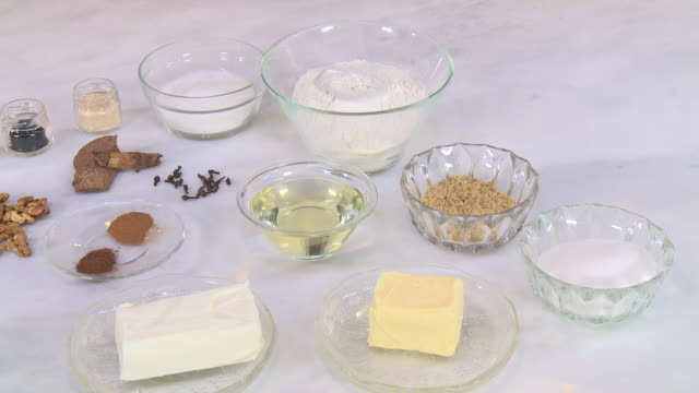 walnut and cinnamon cookie ingredients panleft of sugar flour butter vegetable shortening cinnamon oil yeast walnuts eggs milk and mahleb - sugar stock videos & royalty-free footage