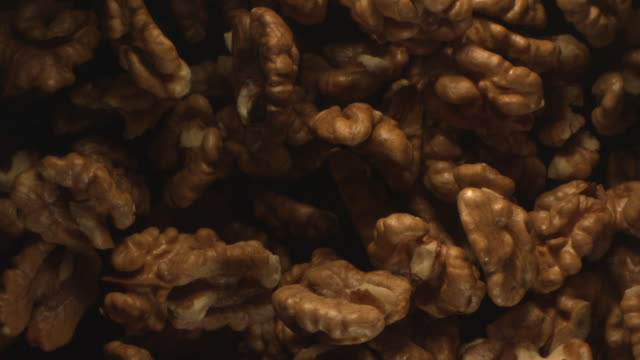 walnut is tossed in the air on a black background - walnut stock videos & royalty-free footage