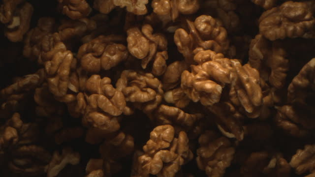 walnut nuts thrown in the air in high speed flying on black background at 1500 fps - walnut stock videos & royalty-free footage