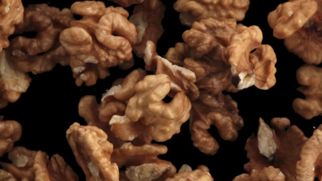 walnuts in the air on black background - walnut stock videos & royalty-free footage
