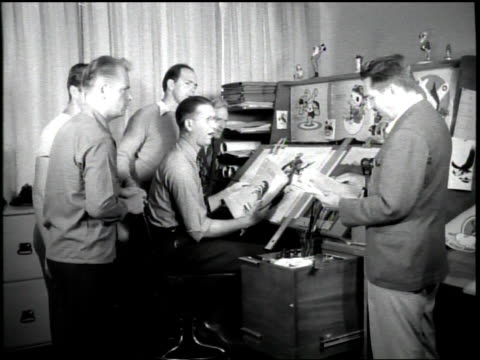 walt disney approches a group of his animators with insignia drawings for the united state military / he draws mickey mouse ears on one / the... - disney stock videos and b-roll footage