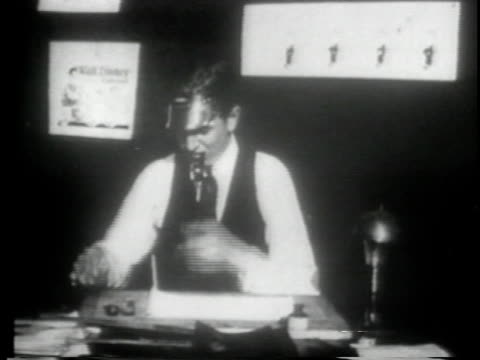 walt disney sitting at drawing desk and lighting pipe - 1923 stock-videos und b-roll-filmmaterial