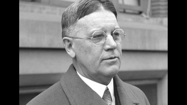 Walter F Brown wearing octagonal eyeglass frames stands outdoors wearing an overcoat he is Pres Herbert Hoover's newly appointed Postmaster General /...