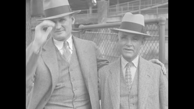 walter johnson and washington senators president clark griffith wearing suits and hats standing outside fence / ms johnson and griffith johnson's arm... - hat stock videos & royalty-free footage