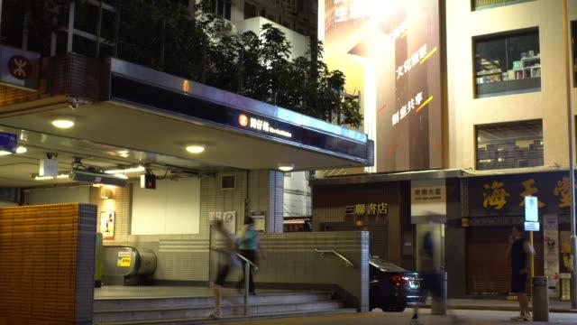 stockvideo's en b-roll-footage met wan chai mtr exit bij night man roken - spoorlijn
