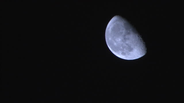 waning gibbous moon softly glowing in the night sky - half moon stock videos & royalty-free footage