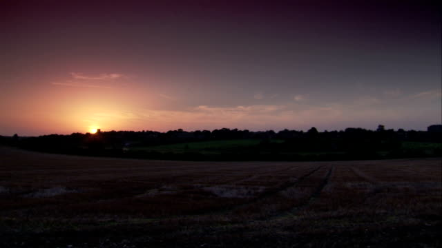 A waning sun casts rosy light across the English countryside. Available in HD.