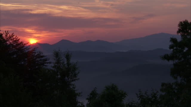a waning sun casts rosy light across the wooded appalachian mountains. - appalachia stock videos & royalty-free footage