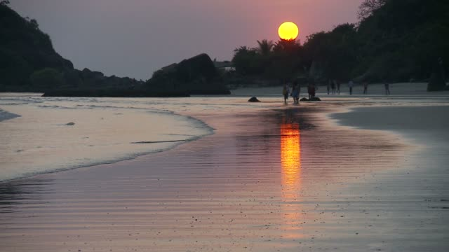 A waning sun casts rosy light over Palolem Beach, India.