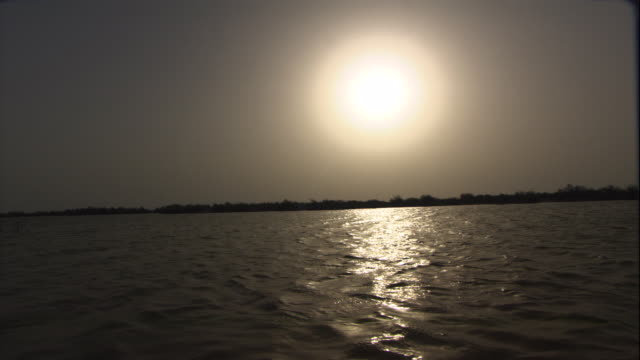 a waning sun glows above a rippling river. - senegal stock videos & royalty-free footage