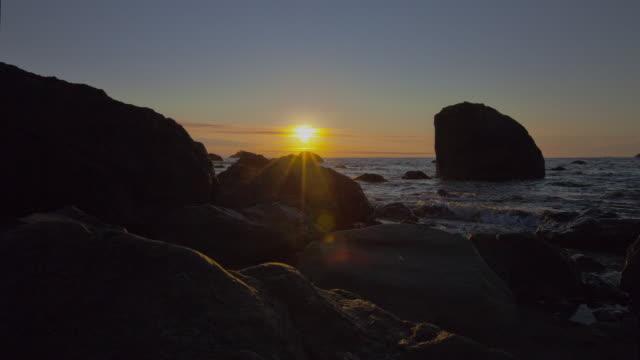 vídeos de stock, filmes e b-roll de a waning sun sets beyond the rippling big lagoon in redwood national park. - parque nacional de redwood