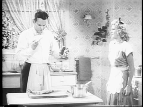war film bulletin number five / blondie and dagwood in kitchen cooking dagwood opens tin can and throws it in trash / blondie grabs it back out and... - psa stock videos & royalty-free footage