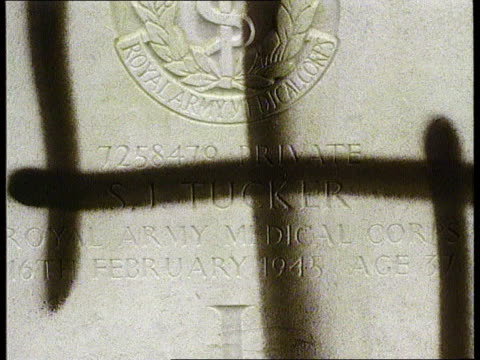 vidéos et rushes de war grave desecration holland nijmegen ms war graves daubed with swastikas pan lr cs swastika daubed on gravestone tilt cs ditto ms line of graves... - pierre tombale