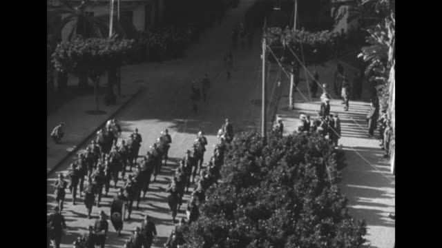 vídeos de stock, filmes e b-roll de war memorial in algiers with bunting around its base / tiltdown shot small military parade to the memorial / french adm francois darlan at left walks... - áfrica do norte